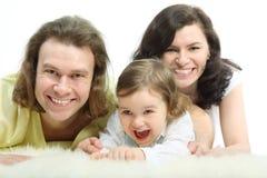 La giovane famiglia felice sta trovando su pelliccia fotografia stock libera da diritti