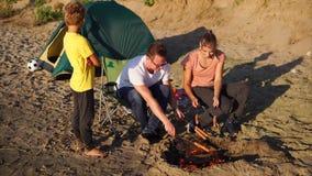 La giovane famiglia frigge le salsiccie su fuoco sulla spiaggia un giorno di estate ventoso video d archivio
