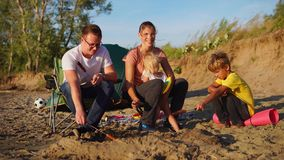 La giovane famiglia frigge le salsiccie sugli spiedi su fuoco sulla spiaggia un giorno di estate ventoso archivi video