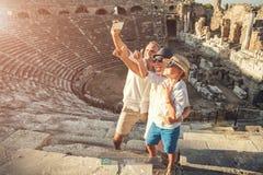 La giovane famiglia positiva prende una foto di auto sull'anfiteatro antico Fotografie Stock Libere da Diritti