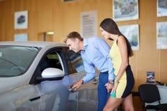 La giovane famiglia sceglie la nuova automobile in una sala d'esposizione Sfera differente 3d Fotografia Stock Libera da Diritti