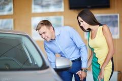 La giovane famiglia sceglie la nuova automobile in una sala d'esposizione Sfera differente 3d Immagine Stock