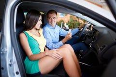 La giovane famiglia sceglie la nuova automobile in una sala d'esposizione Sfera differente 3d Immagini Stock