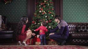 La giovane famiglia si siede vicino all'albero di Natale ricco È ghirlanda decorata, giocattoli, nastri, archi Mamma, papà ed il  video d archivio
