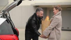 La giovane famiglia sta imballando le sue borse di drogherie alla nuova automobile Uomo di Front View Of Handsome Bearded e bella video d archivio