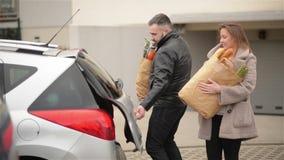 La giovane famiglia sta imballando le sue borse di drogherie alla nuova automobile Uomo di Front View Of Handsome Bearded e bella stock footage