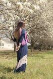 La giovane femmina adulta che sta fra il fiore dell'albero sboccia Fotografia Stock Libera da Diritti