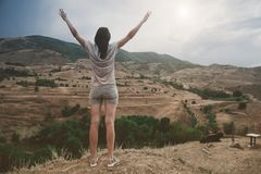 La giovane femmina attraente sta praticando l'yoga sulla cima dell'alta montagna nella sera Immagine Stock