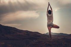 La giovane femmina attraente sta praticando l'yoga sulla cima dell'alta montagna nella sera Immagini Stock