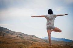 La giovane femmina attraente sta praticando l'yoga sulla cima dell'alta montagna nella sera Fotografia Stock