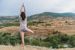 La giovane femmina attraente sta praticando l'yoga sulla cima dell'alta montagna nella sera Fotografia Stock Libera da Diritti