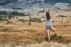 La giovane femmina attraente sta praticando l'yoga sulla cima dell'alta montagna nella sera Immagine Stock Libera da Diritti