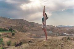 La giovane femmina attraente sta praticando l'yoga sulla cima dell'alta montagna nella sera Immagini Stock Libere da Diritti