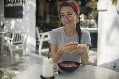 La giovane femmina caucasica felice utilizza il suo telefono quando ha prima colazione in caffè, fotografia stock libera da diritti