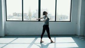 La giovane femmina esegue un backflip con le mani nella donna flessibile di stodio di ballo che fa le spaccature nello sguardo di video d archivio