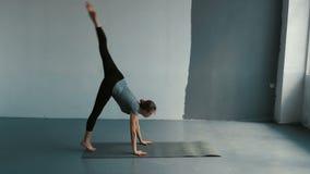 La giovane femmina esegue un backflip con le mani nella sala da ballo spaziosa Donna flessibile che fa le spaccature in studio stock footage