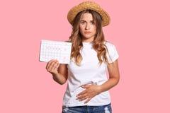 La giovane femmina europea dispiaciuta ritiene il dolore e lo spasmo durante il periodo di mestruazione, tiene il calendario, tie fotografia stock libera da diritti