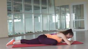 La giovane femmina fa l'esercizio d'allungamento difficile sulla stuoia della palestra mentre si prepara nella palestra Fotografia Stock
