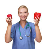 La giovane femmina graziosa tiene la mela ed il pepe rossi Immagini Stock