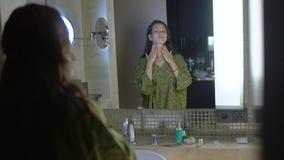 La giovane femmina nei supporti della vestaglia vicino allo specchio in bagno, prende la cura di pelle video d archivio