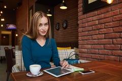 La giovane femmina sta guardando il video sulla compressa digitale durante il resto in caffetteria moderna Immagini Stock