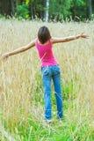 La giovane femmina sta nel campo del raccolto Fotografie Stock