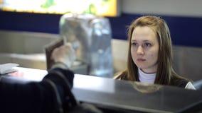 La giovane femmina sta sedendosi nel funzionamento di area reception dell'aeroporto video d archivio