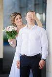 La giovane fine sposata allegra della sposa osserva al suo sposo Fotografie Stock