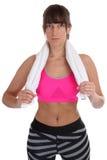 La giovane forma fisica mette in mostra il ritratto della donna di allenamento con l'asciugamano isolato Immagini Stock