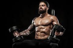 La giovane forma fisica muscolare mette in mostra l'allenamento dell'uomo con il bilanciere nella palestra di forma fisica Immagini Stock Libere da Diritti