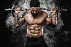 La giovane forma fisica muscolare mette in mostra l'allenamento dell'uomo con il bilanciere nella palestra di forma fisica Immagine Stock