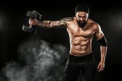 La giovane forma fisica muscolare mette in mostra l'allenamento dell'uomo con il bilanciere nella palestra di forma fisica Fotografie Stock