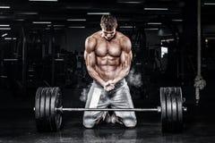 La giovane forma fisica muscolare mette in mostra l'allenamento dell'uomo con il bilanciere nella palestra di forma fisica Fotografie Stock Libere da Diritti