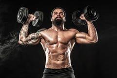 La giovane forma fisica muscolare mette in mostra l'allenamento dell'uomo con la testa di legno nella palestra di forma fisica Immagine Stock