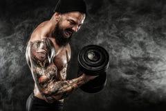 La giovane forma fisica muscolare mette in mostra l'allenamento dell'uomo con la testa di legno nella palestra di forma fisica Fotografie Stock Libere da Diritti