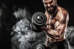 La giovane forma fisica muscolare mette in mostra l'allenamento dell'uomo con la testa di legno nella palestra di forma fisica Immagini Stock