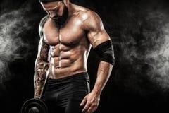 La giovane forma fisica muscolare mette in mostra l'allenamento dell'uomo con la testa di legno nella palestra di forma fisica Immagine Stock Libera da Diritti