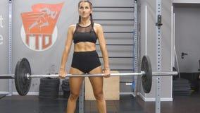 La giovane forte donna con l'ente perfetto in abiti sportivi strappa il peso massimo in palestra Culturista femminile che fa eser video d archivio
