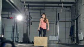 La giovane forte donna con l'ente perfetto di forma fisica in abiti sportivi che fanno l'insieme della scatola salta alla palestr video d archivio