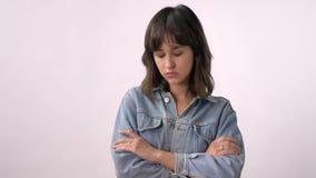 La giovane forte ragazza castana sta stando con le armi attraversate, guardando alla macchina fotografica, fondo bianco stock footage