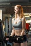 La giovane forte ragazza fa gli esercizi con le teste di legno Fotografia Stock