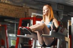 La giovane forte ragazza fa l'ascensore della gamba per l'ABS in palestra Immagini Stock