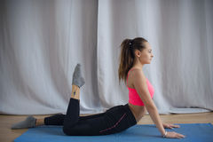 La giovane ginnasta esegue un riscaldamento prima dell'esercizio Immagini Stock Libere da Diritti