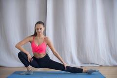 La giovane ginnasta esegue un riscaldamento prima dell'esercizio Immagini Stock