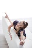 La giovane ginnasta femminile sveglia sta allungando il suo corpo Immagine Stock