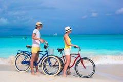 La giovane guida felice delle coppie bikes sulla spiaggia tropicale bianca Fotografia Stock