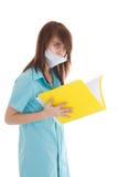 La giovane infermiera attraente con un dispositivo di piegatura isolato Fotografia Stock