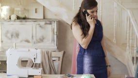 La giovane macchina per cucire vicina della donna del progettista e della cucitrice dell'abbigliamento parla il telefono che sorr archivi video