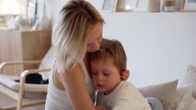 La giovane madre abbraccia un ragazzo gridante nella camera da letto archivi video