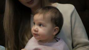 La giovane madre alimenta una bambina con un formaggio di Suluguni video d archivio